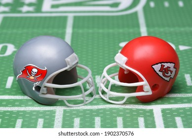IRVINE, CALIFORNIA - 25 JAN 2021: Helmets for the Tampa Bay Buccaneers, and Kansas City Chiefs, opponents in Super Bowl LV. on a green football field background.