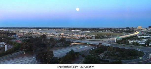 Irvine, California, February 26, 2016: Aerial view of John Wayne Airport in Orange County, California with a full moon at moonset. Editorial use.
