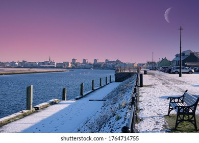 irvine harbour Sreet at sunrise with a red sky a small moon and fresh snow over the town centre.