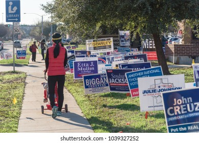 IRVING, TEXAS, USA-MAR 2, 2018: Yard sign at residential street near library for primary election day in Dallas county. Rear view of young Asian lady with stroller on concrete pathway