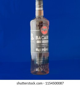 IRVING, TX, US-AUG 4, 2018:Close-up studio shot side view a bottle of Bacardi Black rum isolated on blue. Bacardi Limited is the largest privately held, family-owned spirits company in the world