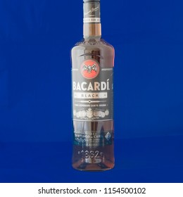 IRVING, TX, US-AUG 4, 2018:Close-up studio shot front view a bottle of Bacardi Black rum isolated on blue. Bacardi Limited is the largest privately held, family-owned spirits company in the world