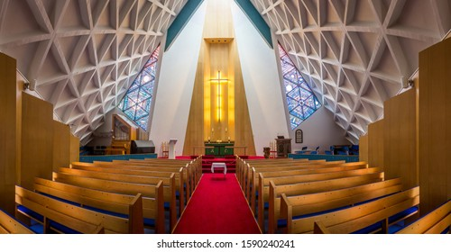 ISAFJORDUR, ICELAND - JULY 30, 2018: Interior of empty  Protestant church. Rows of benches, red carpet and light altar with big cross.