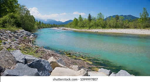 isar river at summertime with mountain view and stone blocks
