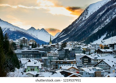 Ischgl, Austria - December 29, 2017: Ischgl in nightfall, view from hill top. Evening in small town in Tyrol Alps. The hole town is snow covered. Yellow church is in the city center