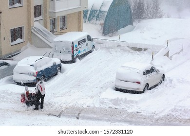 Ischgl/Austria - January 2019: A man cleans snow with a snowplow after a heavy snowfall in alpine village