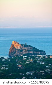"""Ischia Island, Naples - Italy. The red light of dusk colors the """"Castello Aragonese"""" (Aragonese Castle) a medieval castle build on a little island just near the shore od Ischia."""