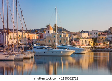 Ischia, Italy - April 20, 2018: Sunset view of Forio, Ischia island, Italy. Town streets with church, yachts, castle of Forio are reflected in serene sea.