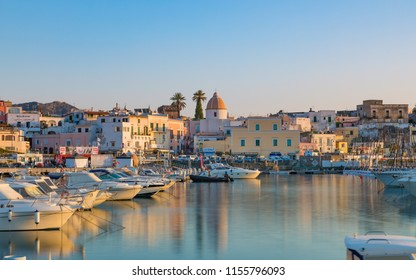 Ischia, Italy - April 20, 2018: Sunset view of Forio, Ischia island, Italy. Town streets with church, castle of Forio are reflected in serene sea. Photo was taken with very long exposure.