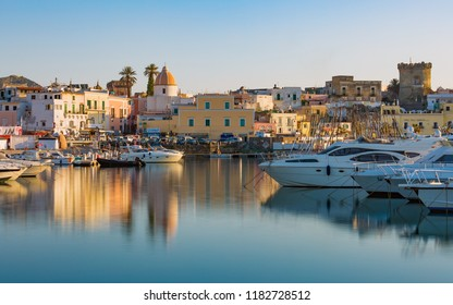 Ischia, Italy - April 20, 2018: Sunset view of Forio, Ischia island, Italy. Town streets with church, castle of Forio are reflected in serene sea.