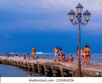 ISCHIA, ITALY - AUGUST 16, 2018: People on the seaside on the Island of Ischia, Gulf of Naples.