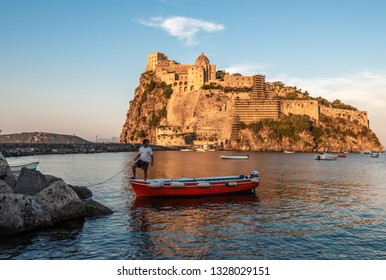 Ischia, Italy June 20, 2017: Boatman with a boat on the background of the Aragonese castle.