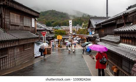 ISE, JAPAN - MARCH 21, 2017 : Visitors walking in the rain at Okage Yokocho, which is a small district in Oharaimachi, which recreates a townscape of past centuries, lined by shops and restaurants.