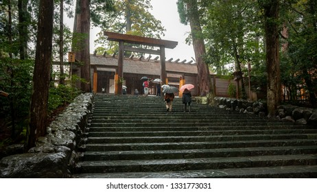 ISE, JAPAN - MARCH 21, 2017 : Worshipers and visitors walking on stone steps leading to the main shrine, called Naiku, in the rain at Ise Grand Shrine, which is Japan's most sacred Shinto shrine.