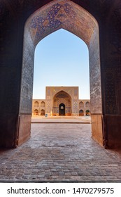 Isfahan, Iran - 23 October, 2018: Amazing view of courtyard of the Shah Mosque (Imam Mosque) through scenic arch. Wonderful Persian exterior of the Muslim place. Awesome Islamic architecture.