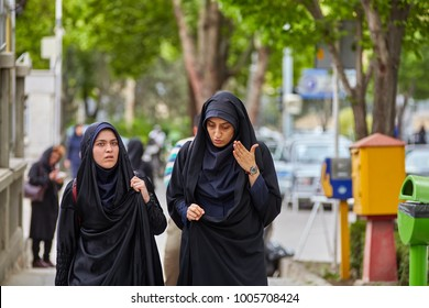 Isfahan, Iran - April 24, 2017: Two Muslim women, dressed in a black Islamic chador, talk while walking along the city street.