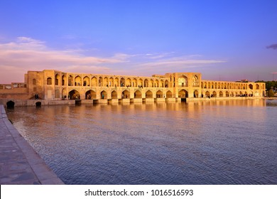 Isfahan, Iran - April 24, 2017: Arched stone pedestrian bridge across the river Seyende-Rud is illuminated by the light of the setting sun.