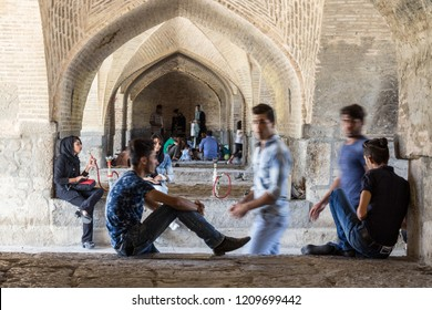 ISFAHAN, IRAN - AUGUST 20, 2016 : Iranian Youngsters gathering under Si o Seh Pol Bridge smoking hookah and using smartphones. Si o Seh Pol is one of the main bridges of the city