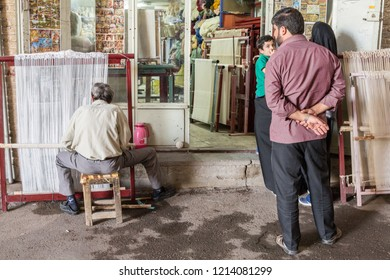 ISFAHAN, IRAN - AUGUST 20, 2016: Iranian family looking at a worker producing a rug on a weawing loom in his shop. Carpets are one of the main iconic exports of the iranian economy