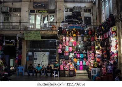 ISFAHAN, IRAN - AUGUST 20, 2018: Street of the Isfahan bazar in the afternoon, with merchants sitting and selling school backpacks in the covered market.