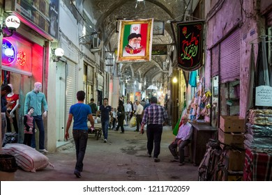 ISFAHAN, IRAN - AUGUST 20, 2018: Street of the Isfahan bazar with an Iranian flag hanging with the portraits of the 2 Supreme leaders of the Islamic Republic of Iran, Ali Khamenei & Ruhollah Khomeini