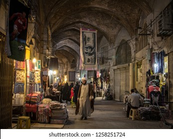 ISFAHAN, IRAN - AUGUST 20, 2018: Islam passing under a towel shaped like a US Dollar bill in the Isfahan bazar in the evening. The iranian rial, iran currency, is being devaluated facing the dollar