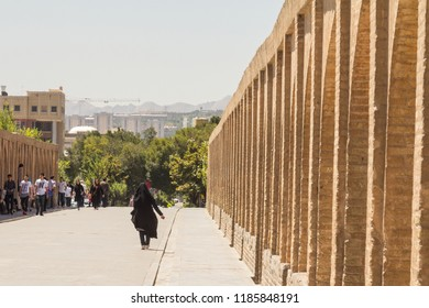 ISFAHAN, IRAN - AUGUST 7, 2015: iranian woman wearing the traditional muslim black veil waling on Si o Seh Pol bridge. Also known as Allahverdi Khan Bridge,  it is a major landmark of the city
