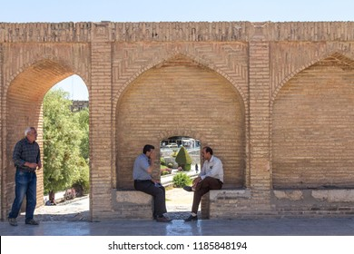 ISFAHAN, IRAN - AUGUST 7, 2015: Senior iranian people, men, sitting and discussing on the archs of the Si o Seh Pol, one of the main bridges of the city and a major landmark