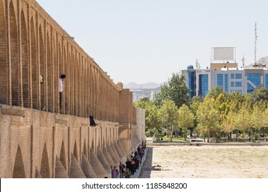 ISFAHAN, IRAN - AUGUST 7, 2015: Iranian people passing by on the Si o Seh Pol bridge on the afternoon in Isfahan, Iran. Also known as Allahverdi Khan Bridge, it is a major landmark of the city