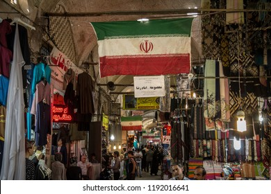 ISFAHAN, IRAN - AUGUST 8, 2018: Street of the Isfahan bazar with an Iranian flag hanging, in a covered alley of the market. Symbol of the Persian architecture, it's a major landmark of the city