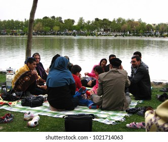Isfahan, Iran - March 24, 2010: People picnicking outdoors on the green lawns near Si-o-Se-pol bridge during Iranian festival Sizdah Bedar, or Nature's Day, which marks the end of the Nowruz holiday.