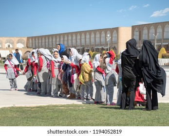 Isfahan, Iran - March 4, 2017 : primary school children with islamic veil visiting Naqsh-e Jahan square, a UNESCO famous site