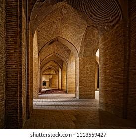 ISFAHAN, IRAN - MAY 8, 2015: Old chamber of Taj al Molk at the Jameh Mosque beautiful interior with the brick pillars.