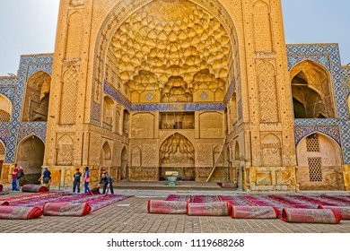 ISFAHAN, IRAN - MAY 8, 2015: Visitors at the inner courtyard where the sun drying cleaned praying carpets at the Jameh Mosque east iwan.