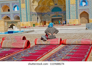 ISFAHAN, IRAN - MAY 8, 2015: Visitors at the inner courtyard where the sun drying cleaned praying carpets at the Jameh Mosque.