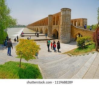 ISFAHAN, IRAN - MAY 8, 2015: People enjoying the view of the Zayandeh river from the ancient Khaju bridge.