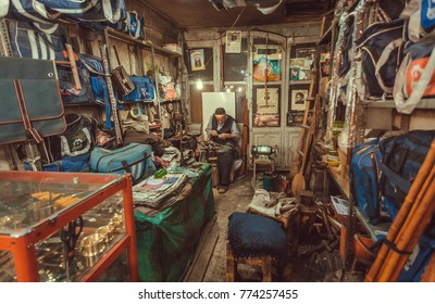 ISFAHAN, IRAN - OCT 14: Elderly man fixing shoes and bags in his workshop on city market on October 14, 2017. The 3rd largest city of Iran, Isfahan is example of Iranian Islamic culture
