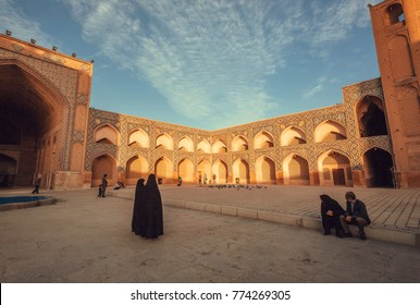 ISFAHAN, IRAN - OCT 14: Women in dark muslim dress walking past a historical persian mosque with courtyard on October 14, 2017. The 3rd largest city of Iran, Isfahan is an example of Islamic culture