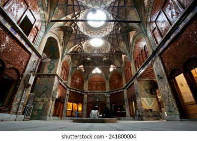 ISFAHAN, IRAN - OCT 16: Two women sit inside courtyard of beautiful Bazaar on October 16, 2014. Bazaar of Isfahan is one of the oldest and largest bazaars in Middle East, dating back to 17th century