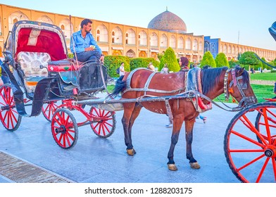 ISFAHAN, IRAN - OCTOBER 19, 2017: The coachman sit on its horse drawn carriage and wait for a clients in Nashq-e Jahad Sqaure, on October 19 in Isfahan