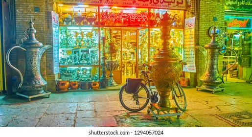 ISFAHAN, IRAN - OCTOBER 19, 2017: The bright showcases of historical metalware dish shop with huge dallahs (coffee pots) and samovar at the entrance, on October 19 in Isfahan
