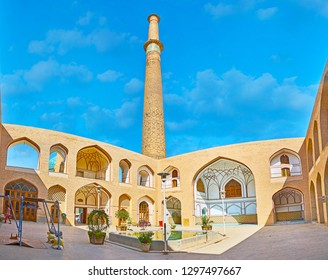 ISFAHAN, IRAN - OCTOBER 21, 2017: Panorama of the courtyard (sahn) of Imam Ali Mosque with tall brick minaret, fountain and arched terrace on background, on October 21 in Isfahan.