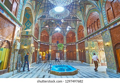 ISFAHAN, IRAN - OCTOBER 21, 2017: The ornate interior of medieval Timche-ye Malek caravanserai of Grand (Soltani) Bazaar with carved wooden panels and rich tiling, on October 21 in Isfahan.