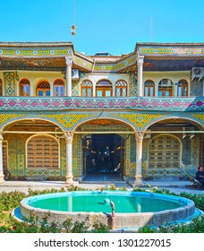 ISFAHAN, IRAN - OCTOBER 21, 2017: The ornate veranda of Timche-ye Malek caravanserai of Grand (Soltani) Bazaar with traditional tiling, slender pillars and fountain, on October 21 in Isfahan.