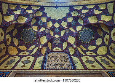 ISFAHAN, IRAN - OCTOBER 21, 2017: The arch of portal (iwan) of Honar Bazaar is decorated with brick muqarnas and covered with bright stellar pattern and Persian calligraphy, on October 21 in Isfahan.