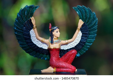 Isis Goddess of the Ancient Egypt Religion outside  in nature and green background