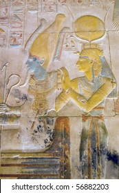 Isis and Osiris carving .  Isis is wearing the horned crown of Hathor.  Inner wall at the Temple to Osiris at Abydos, Egypt.