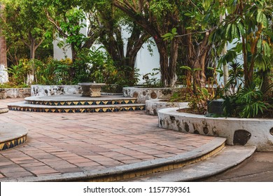 Isla Cuale walk in Puerto Vallarta Mexico with brick pavers, various jungle trees and large building with planters.