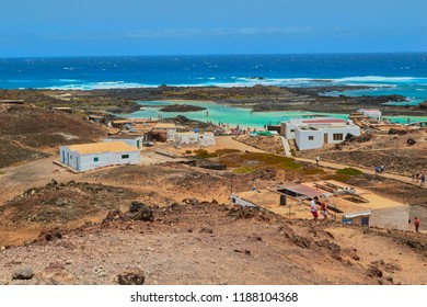 Isla de Lobos, Fuerteventura, Spain; July 5 2018: Nice view of white fisherman houses and people bathing and sunbathing on the blue water beach in Isla de Lobos, Fuerteventura, Canary Islands, Spain
