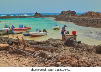 Isla de Lobos, Fuerteventura, Spain; July 5 2018: Fishermen working in the calm and crystal clear sea and small mountains background in Isla de Lobos, Fuerteventura, Canary Islands, Spain